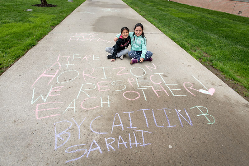 Two young girls sitting on sidewalk with 'Here at Horizons We Respect Each Other' written in chalk